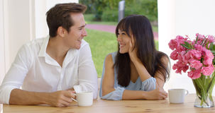 Lachende junge erwachsene Paare, die bei Tisch sitzen stockfotografie
