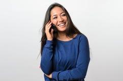 Lachende junge Frau, die auf einem Mobile spricht Stockfotos