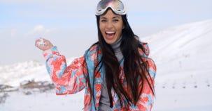 Lachende junge Frau, die einen Schneeball wirft lizenzfreie stockbilder