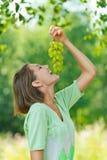 Lachende junge Frau, die Trauben isst Lizenzfreie Stockbilder