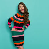 Lachende junge Frau im vibrierenden Kleid blinzelt Lizenzfreie Stockfotos