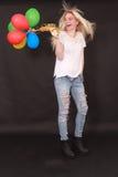 Lachende junge Frau mit Luftballonen in der Hand Lizenzfreie Stockfotos