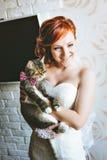 Lachende junge Frau pflegen das Halten einer Katze im rosa Schmetterling lizenzfreie stockfotografie
