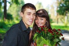 Lachende junge Paare der Liebhaber des Porträts mit einem Blumenstrauß der Rotrose Lizenzfreie Stockfotos