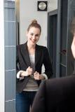 Lachende junge schöne Geschäftsfrau, die ihre erfolgreiche Arbeitsklage überprüft Lizenzfreies Stockfoto