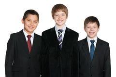 Lachende Jungen in den schwarzen Anzügen Stockfoto