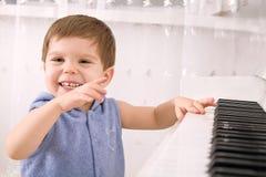 Lachende Jungenspiele auf einem weißen Klavier lizenzfreie stockfotografie