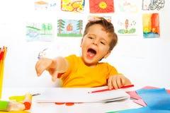 Lachende Jungenzeichnung mit Bleistift auf dem Papier Stockbild