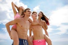 Lachende kameraden die in zwembroek mooie meisjes op een kust op een vage natuurlijke achtergrond houden Stock Fotografie