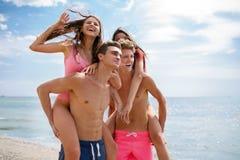 Lachende kameraden die in zwembroek mooie meisjes op een kust op een vage natuurlijke achtergrond houden Royalty-vrije Stock Afbeeldingen
