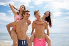Lachende kameraden die in zwembroek mooie meisjes op een kust op een vage natuurlijke achtergrond houden Stock Afbeeldingen