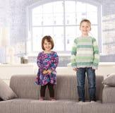 Lachende Kinder, die auf Couch stehen Lizenzfreie Stockbilder