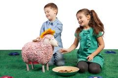 Lachende Kinder, die mit einem Spielzeugschaf spielen Stockbild
