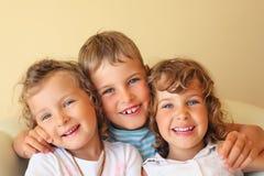 Lachende kinderen drie samen in comfortabele ruimte Royalty-vrije Stock Afbeeldingen