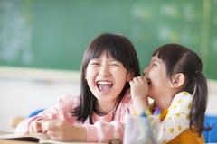 Lachende kleine Mädchen, die Geheimnisse in der Klasse teilen Stockbilder