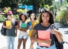 Lachende lateinamerikanische Studentin, die Daumen mit Gruppe zeigt Lizenzfreies Stockfoto