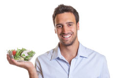 Lachende Latijnse mens die verse salade voorstellen stock foto