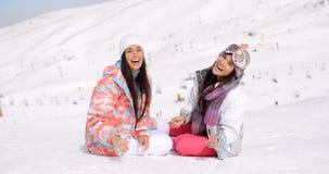 Lachende lebhafte junge Frauen im Schnee lizenzfreie stockfotos