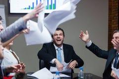 Lachende Leute bei Tisch, die Papiere werfen Stockfotografie
