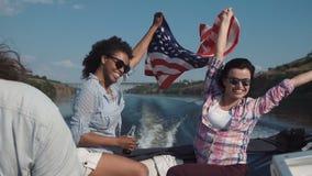 Lachende Mädchen, die in ein Schnellboot mit Flagge reiten stock footage