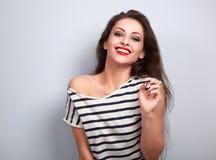 Lachende make-up jonge vrouw die in vrijetijdskleding op blauwe backg kijken Stock Foto's