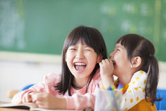 Lachende meisjes die geheimen in klasse delen Stock Afbeeldingen