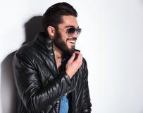 Lachende mens in leerjasje die zijn baard trekken Royalty-vrije Stock Foto's
