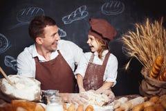 Lachende mens met dochter die brood maken Royalty-vrije Stock Foto