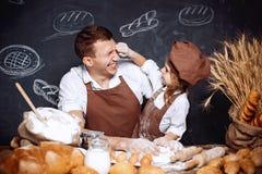 Lachende mens met dochter die brood maken Stock Afbeeldingen