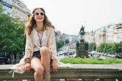 Lachende modische Hippiefrau, die auf Steingeländer in Prag sich entspannt Lizenzfreie Stockfotos