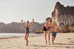 Lachende Moeder en haar aanbiddelijke kinderen die langs een strand lopen stock fotografie