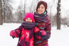 Lachende Mutter, Tochter im Winter Stockfotos