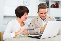Lachende Mutter und Sohn betrachten Software auf Laptop Stockfotografie