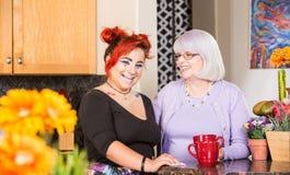 Lachende Mutter und Tochter in der Küche Lizenzfreie Stockfotografie