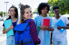 Lachende noordelijke Europese vrouwelijke student met groep vrienden stock afbeelding