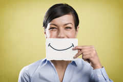 Lachende onderneemster die lege witte kaart voor haar mond houden royalty-vrije stock afbeelding