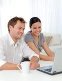 Lachende Paare beim Betrachten des Laptops Stockbild