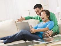 Lachende Paare beim einen Laptop zusammen betrachten Stockfoto