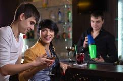 Lachende Paare, die an einem Kneipenzähler trinken Lizenzfreie Stockfotografie