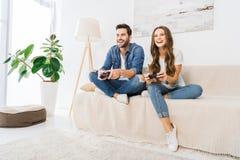 lachende Paare, die Videospiel durch Steuerknüppel auf Sofa spielen stockfotografie