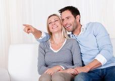 Lachende Paare, die weg vom Schirm zeigen Stockfotografie