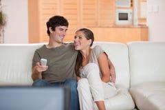 Lachende Paare, die zusammen lustigen Film überwachen stockfotos