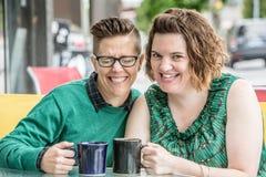 Lachende Paare draußen im grünen Kleid und in der Strickjacke Stockbilder