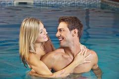 Lachende Paare im Swimmingpool lizenzfreies stockbild