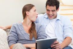 Lachende Paare unter Verwendung eines Tablettecomputers Stockfoto
