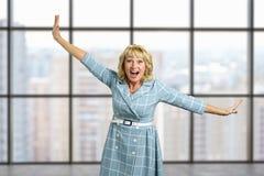Lachende rijpe vrouw op de achtergrond van het bureauvenster Stock Foto's