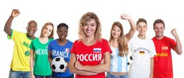 Lachende Russische voetbalverdediger met ventilators van andere landen stock foto