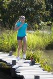 Lachende schöne junge blonde Frau, die zum Spaß läuft und springt Stockfoto