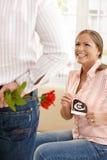 Lachende schwangere Frau, die Blumen erhält Lizenzfreies Stockbild