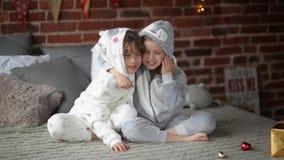 Lachende siblings in bed bij Kerstmis, broer en zusteromhelzingen op Kerstmisochtend stock videobeelden